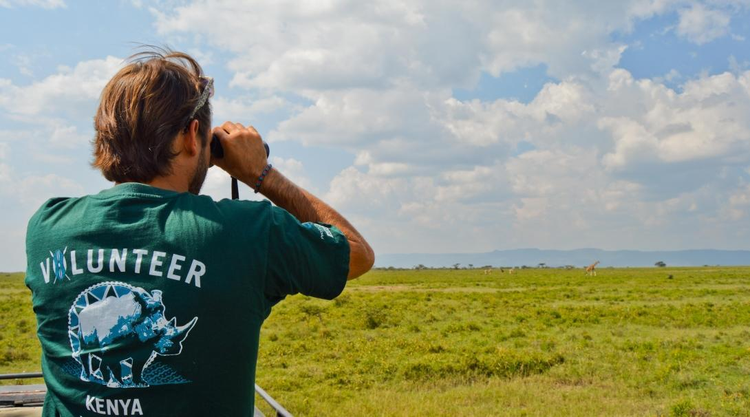 A Projects Abroad volunteer in Kenya is looking at wildlife through his binoculars.